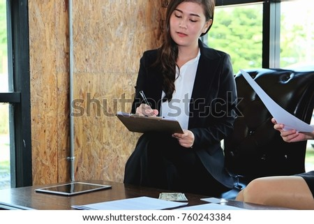 Two businesswoman working together about documents, partner discuss plan or idea and opinion meeting, Asian bussiness are discussing their working on a wood table beside window at coffee shop  #760243384