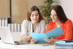 Two businesswomen consulting a report together on a desk at office