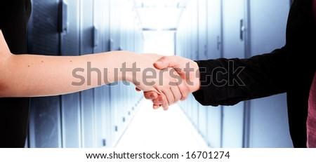 Two businesswomen handshake in a data center