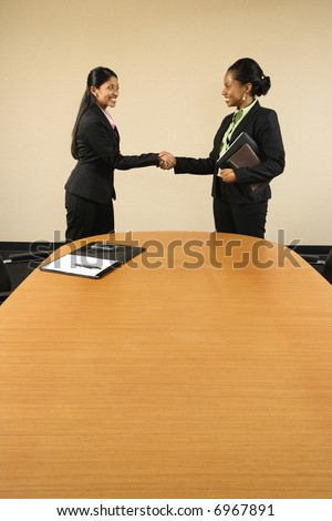 Two businesswomen in suits shaking hands and smiling.