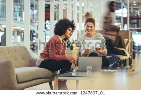 Two businesswomen looking at a paper discussing work at office. Smiling businesswoman sitting with coworker in office with a laptop in front. #1247807101