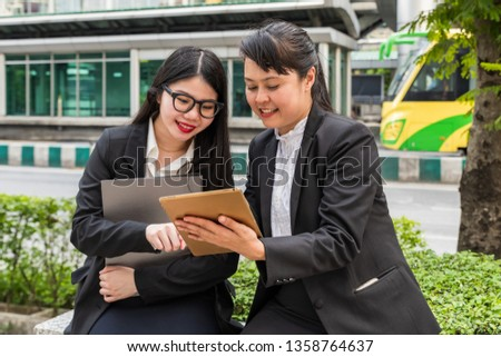 Two businesswomen looking at tablet while holding paper file holder with cityscape as background #1358764637