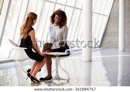 Two Businesswomen Meeting In Reception Of Modern Office