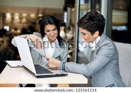Two businesswomen nice discussing on meeting