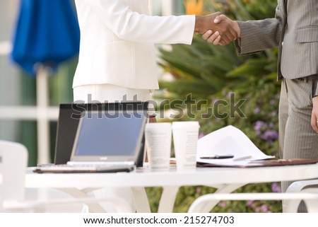 Two businesswomen shaking hands beside pavement cafe table, side view, mid-section