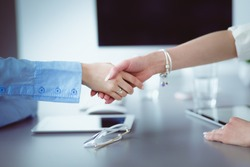 Two businesswomen sitting at a desk shaking hands