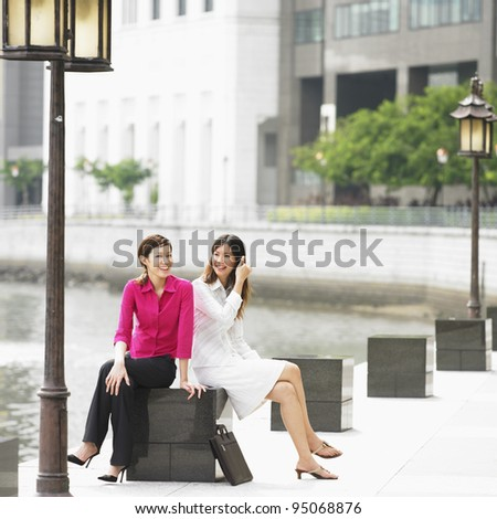 Two businesswomen sitting by water