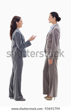 Two businesswomen talking face to face against white background