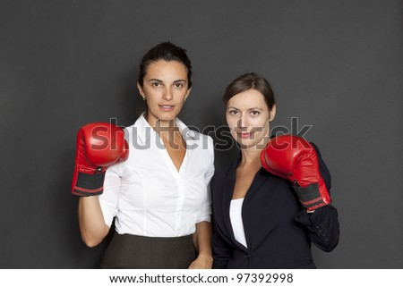 Two businesswomen with red boxing gloves - stock photo
