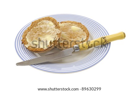 Two buttered whole wheat English muffins on a plate with knife on a white background.