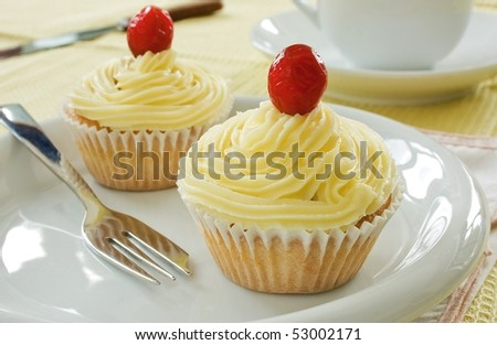 Two buttermilk iced cupcakes on a white plate with a fork - stock photo