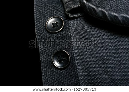 two buttons in a  jeans shirt