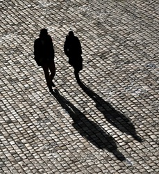 Two bystanders walking on a paved road, projecting their shadows.