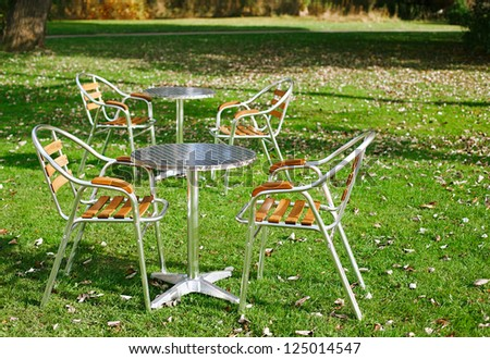 two cafe tables in a park on green grass