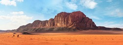Two camels, walking on orange red sand of Wadi Rum desert, large mountains with blue sky above background