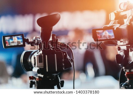 Two cameras recording presentation at press conference, blurred speakers wearing suits background, live streaming concept Foto d'archivio ©