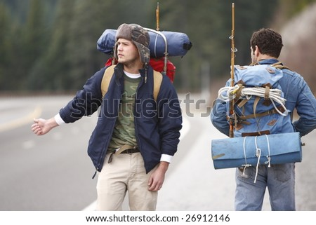 Two campers hitchhiking on a mountain road.