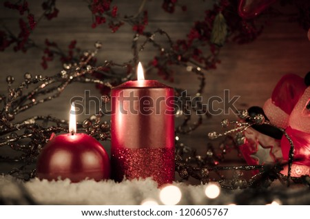 Two candles decorated in a festive Christmas decoration.