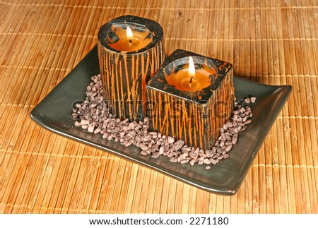 Two candles on a bamboo mat