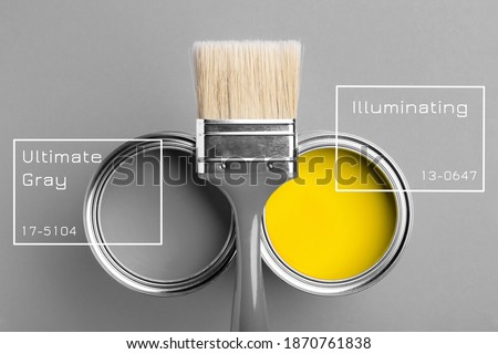 Two cans of yellow and gray paint with gray brush on gray background with inscriptions. Top view, repair concept.