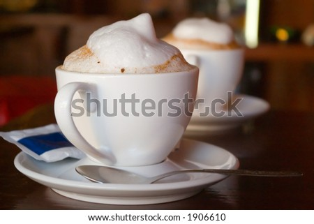 Two cappuccino cups with milk foam and cinnamon