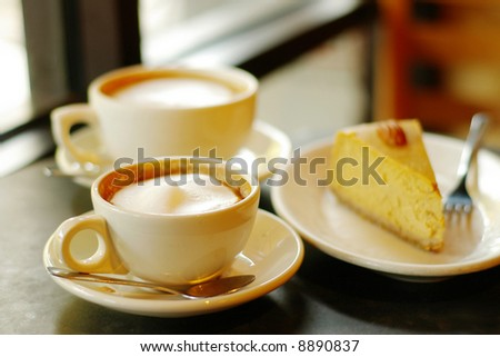 Two cappuccinos and a piece of pumpkin pie
