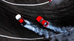 Two car drifting battle on asphalt street road race track with smoke, Aerial view automobile and automotive modify tuning car competition battle with black tire skid mark texture and background.