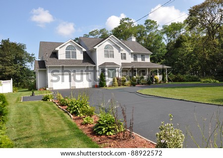Two Car Garage Suburban Home with Long Blacktop Driveway Plants Flower Bed Front Yard Lawn Sunny Blue Sky Clouds Daytime