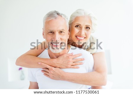 Two carefree, careless people with in pajama, sleep, wear, sleepwear, nightwear grey hair cuddle to each other in comfortable bright room and look at camera