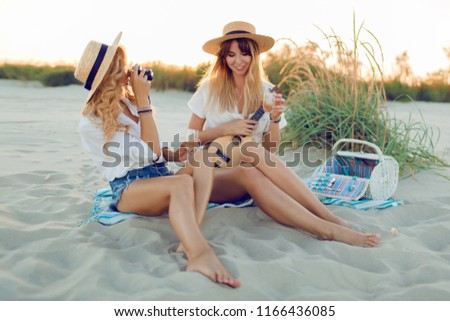 Two carefree happy girls  enjoying a beach party with music and picnic in summer evening. Blonde pretty girl playing ukulele guitar and her friend making picture .
