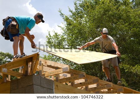 Two carpenters place plywood onto trusses to be nailed down for the roof.