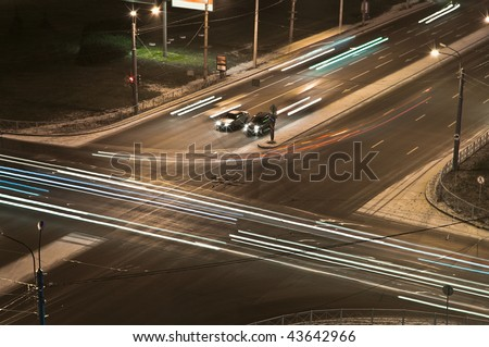 Two cars at a crossroads wait at night a green signal of a traffic light. Night shooting. Bright traces of headlights of cars