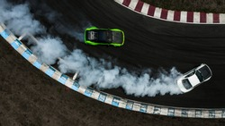 Two cars drifting battle on race track with smoke, Aerial view two car drifting battle.