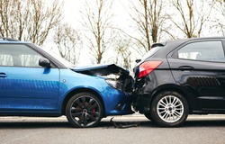 Two cars involved in traffic accident on side of the road with damage to bonnet and fender