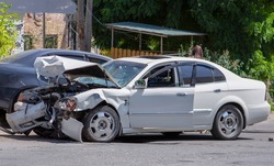 two cars on the road after the collision. Damaged white car on the road after the accident