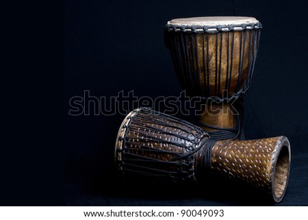 Two carved African djembe drums on dark background.