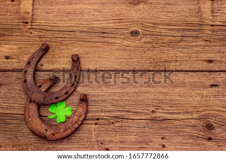 Two cast iron metal horse horseshoes, felt clove leaf. Good luck symbol, St.Patrick's Day concept. Old wooden background, horse accessories, top view