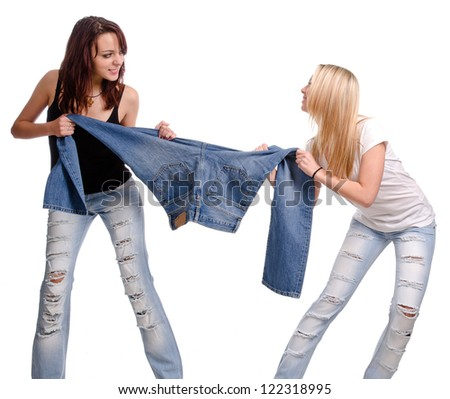 Two casual young women fighting and having a tug of war over a pair of denim jeans, studio portrait isolated on white