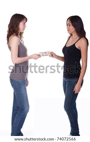 Two casually dressed women standing, exchanging money.