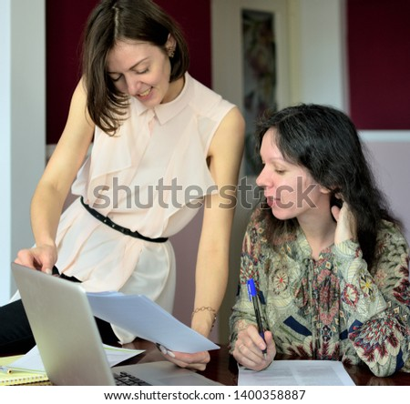 two casually dressed young ladies models sit on a desk in a vintage office and discuss model release documents, group portrait and close-up #1400358887