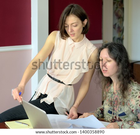 two casually dressed young ladies models sit on a desk in a vintage office and discuss model release documents, group portrait and close-up #1400358890