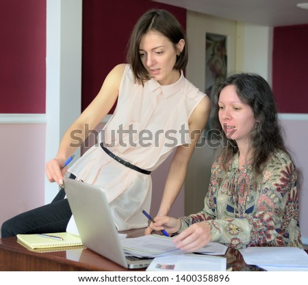 two casually dressed young ladies models sit on a desk in a vintage office and discuss model release documents, group portrait and close-up #1400358896