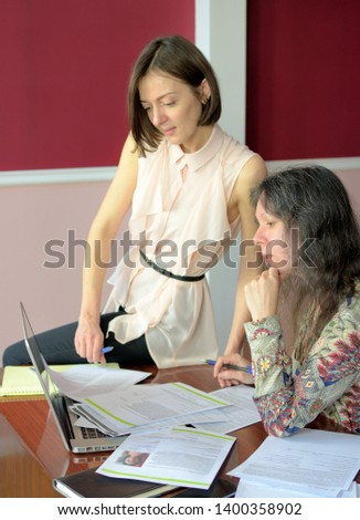 two casually dressed young ladies models sit on a desk in a vintage office and discuss model release documents, group portrait and close-up #1400358902