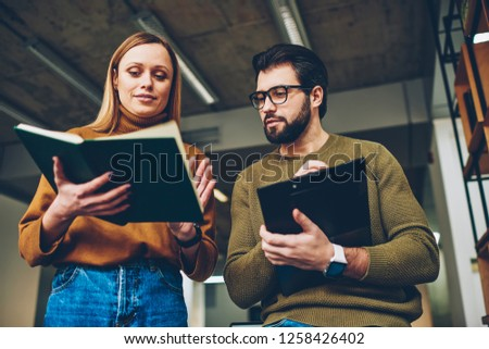 Two casually dressed young office colleagues standing together in modern office looking focused while discussing paperwork, hipsters reading literature at university library during learning
