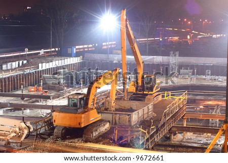 two caterpillar excavators working on construction site in the night