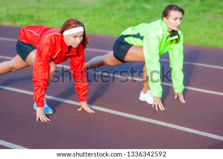 Two Caucasian Athletes Standing Prepared For Running on Track Course.Horizontal image
