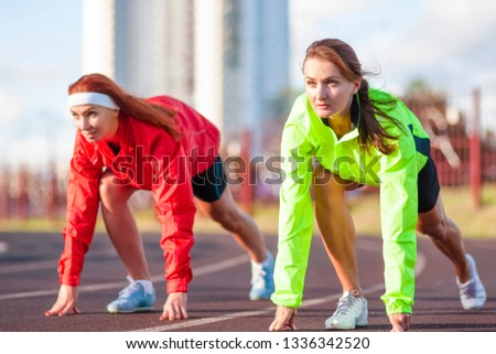 Two Caucasian Athletes Standing Prepared For Running on Track Course.Horizontal image Orientation