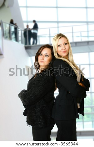 Two caucasian businesswoman standing back to back against interior corporate building. Concept of teamwork and profesionalism.