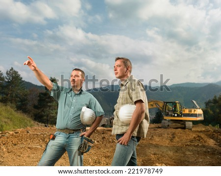 two caucasian engineers standing, one of them pointingat construction in progress