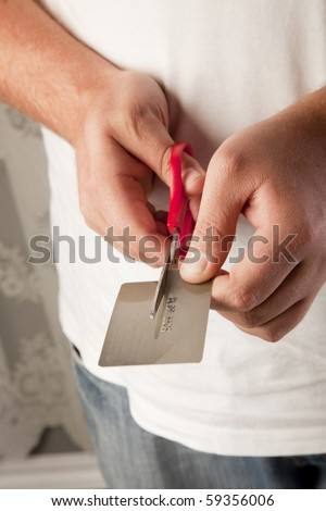 Two caucasian hands using a scissor to cut a credit card in half. The numbers on the card is not real.